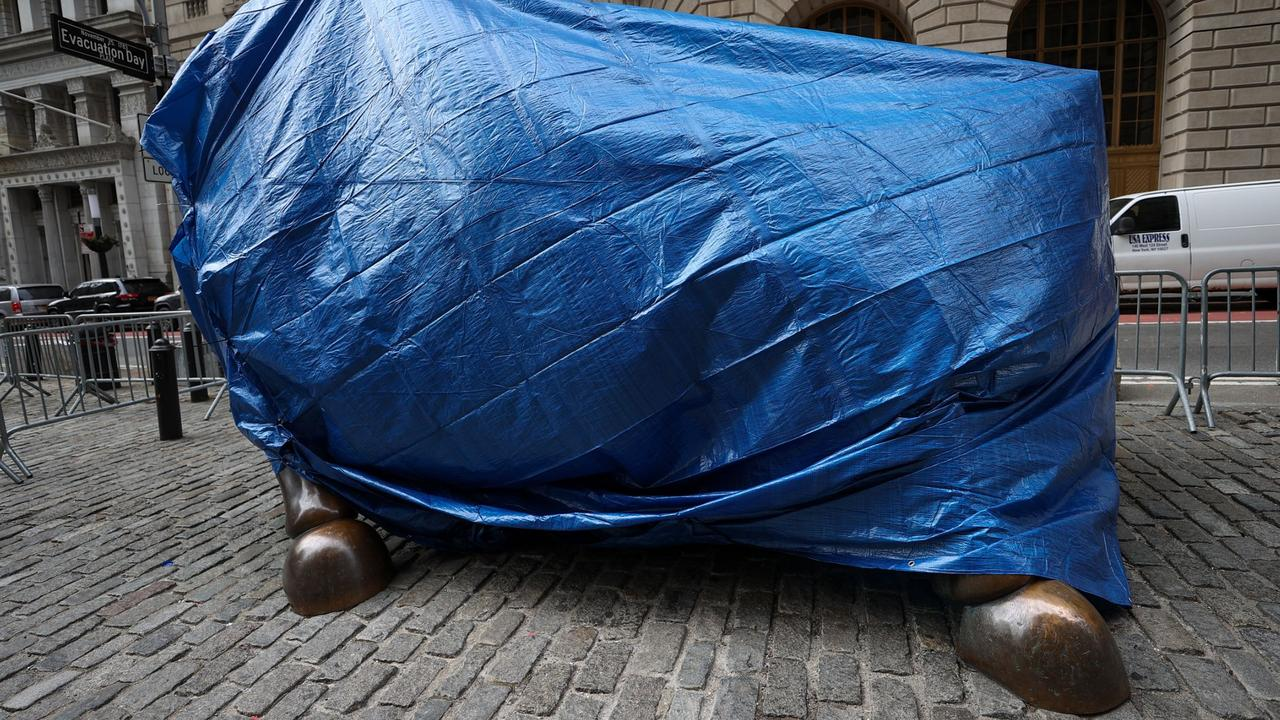 Wall Street Bull statue under guard after being defaced with pieces of tape
